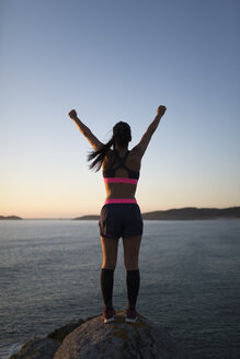 Woman with arms raised in front of a coastal landscape - RAEF02072