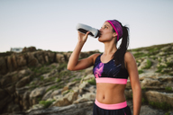 Portrait of an athlete woman drinking water outdoors - RAEF02075