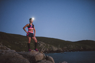 Sportive woman with headlamp standing on rocks in the evening - RAEF02096