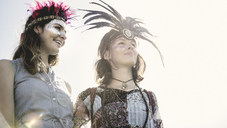 Two young women at a summer music festival faces painted, wearing feather headdresses. - MINF05554