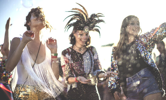 Three smiling young women at a summer music festival face painted, wearing feather headdress, dancing among the crowd. - MINF05560
