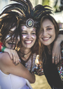 Three young women at a summer music festival wearing feather headdress and faces painted, smiling at camera. - MINF05566