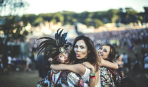 Three young women at a summer music festival feather headdress and faces painted, smiling at camera, sticking out tongue. - MINF05572