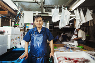 A traditional fresh fish market in Tokyo. A man in a blue apron standing behind the counter of his stall. - MINF05689