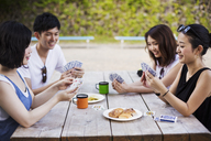 Three young women and a man sitting at a table, playing cards. - MINF05719
