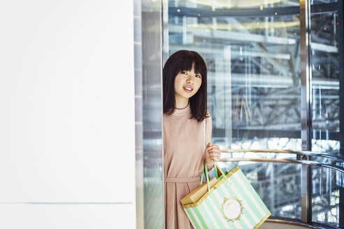 Young woman with long brown hair in a shopping centre, carrying shopping bags. - MINF05749