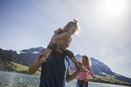 Austria, Tyrol, Walchsee, happy father carrying daughter on shoulders at the lake - JLOF00154