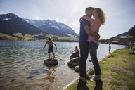 Austria, Tyrol, Walchsee, happy couple embracing at the lake with family in background - JLOF00157