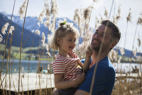 Austria, Tyrol, Walchsee, happy father carrying daughter in reeds at the lakeshore - JLOF00160