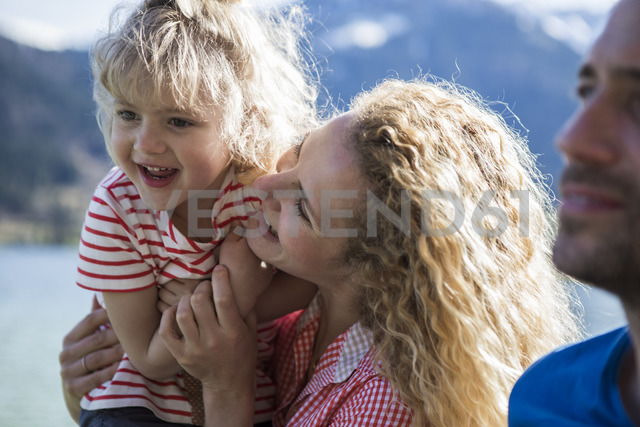 Austria, Tyrol, Walchsee, happy mother carrying daughter at the lake - JLOF00169