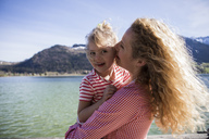 Austria, Tyrol, Walchsee, happy mother carrying daughter at the lake - JLOF00175