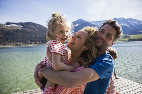 Austria, Tyrol, Walchsee, happy family hugging on a jetty at the lakeside - JLOF00178