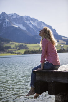 Austria, Tyrol, Walchsee, smiling woman sitting on a jetty at the lake - JLOF00184