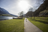 Austria, Tyrol, Walchsee, girl running on path at the lake - JLOF00190