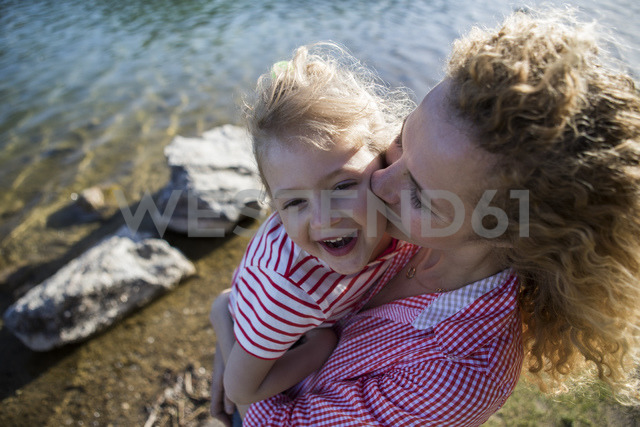 Austria, Tyrol, Walchsee, mother carrying happy daughter at the lake - JLOF00193