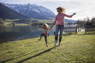 Austria, Tyrol, Walchsee, carefree mother and daughter jumping at the lake - JLOF00199