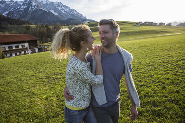 Austria, Tyrol, Walchsee, happy couple hiking on an alpine meadow - JLOF00202