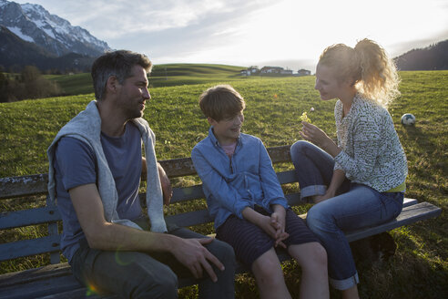 Austria, Tyrol, Walchsee, happy family resting on a bench in the mountains - JLOF00205