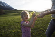 Austria, Tyrol, Walchsee, portrait of girl with mother holding flowers on an alpine meadow - JLOF00208