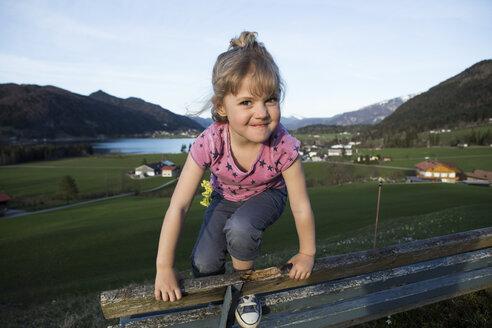 Austria, Tyrol, Walchsee, happy girl on a bench - JLOF00211