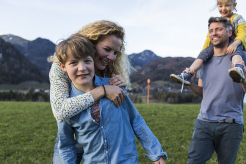 Austria, Tyrol, Walchsee, happy family hiking on an alpine meadow - JLOF00217
