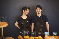 Smiling man and woman wearing baseball cap and apron standing in a bakery, trays with freshly baked goods. - MINF05923