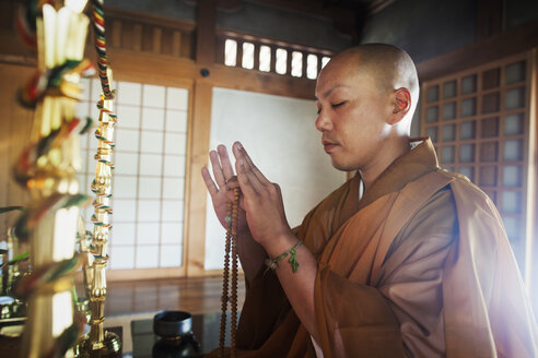 Side view of Buddhist monk with shaved head wearing golden robe kneeling indoors in a temple, holding mala, eyes closed. - MINF05956