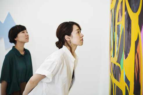 Two women standing in an art gallery, looking at an abstract modern painting. - MINF05968