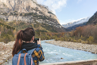 Spain, Ordesa y Monte Perdido National Park, back view of woman with backpack taking photo - AFVF01291