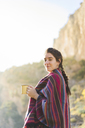 Spain, Alquezar, portrait of smiling young woman with coffee mug in nature - AFVF01312