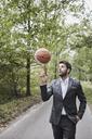 Businessman balancing basketball on rural road - RORF01364
