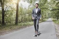 Businessman riding skateboard on rural road - RORF01367
