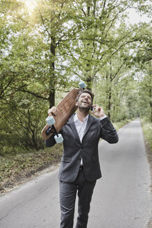 Happy businessman with skateboard talking on smartphone on rural road - RORF01370