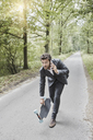 Businessman walking with skateboard and smartphone on rural road - RORF01373