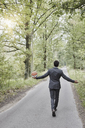 Rear view of businessman walking with basketball on rural road - RORF01376