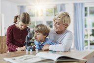 Mother with daughter and son using microscope at home - RORF01388