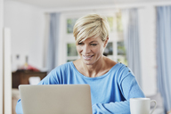 Woman using laptop at home - RORF01391