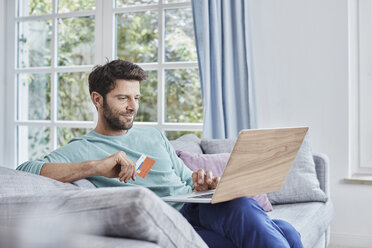 Smiling man at home shopping online - RORF01397