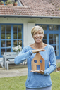 Portrait of smiling woman standing in front of her home holding house model - RORF01406