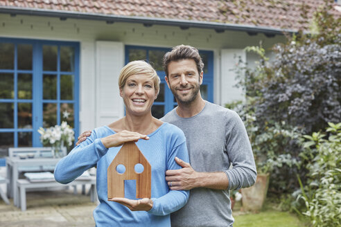 Portrait of smiling couple standing in front of their home holding house model - RORF01409