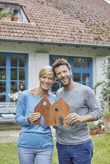 Portrait of smiling couple standing in front of their home holding house model - RORF01412