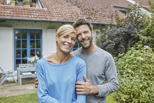 Portrait of smiling couple standing in front of their home - RORF01418