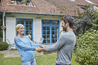 Happy couple dancing in front of their home - RORF01421