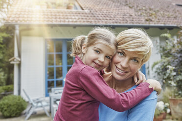 Portrait of smiling mother carrying daughter in front of their home - RORF01427
