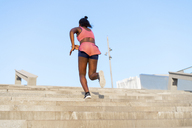 Young woman during workout on stairs, climbing stairs - AFVF01316