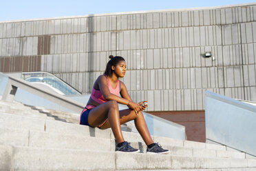 Young sportive woman using smartphone sitting on step - AFVF01322