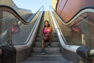 Young sportive woman sitting on escalator - AFVF01334