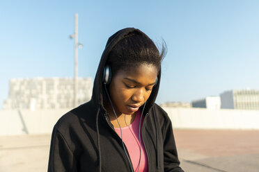 Young sportive woman listening music with headphones - AFVF01343