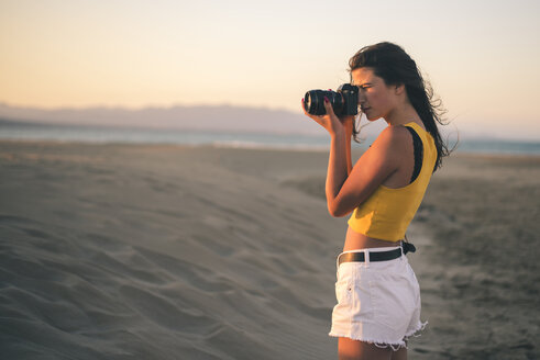 Teenage girl taking photos with camera on the beach at sunset - ACPF00154