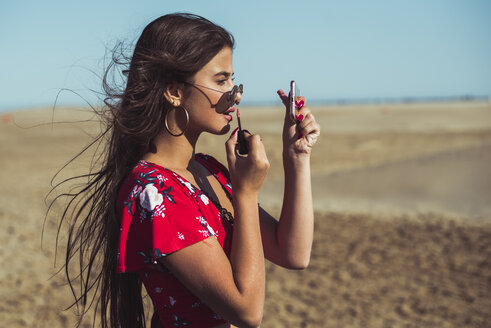 Teenage girl applying lip gloss on the beach - ACPF00160
